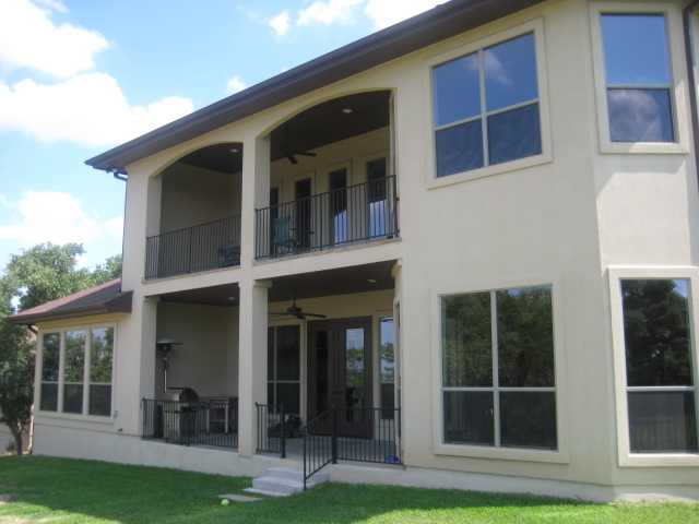 Rear exterior view showing the covered porch and balcony framed with wrought iron railings.
