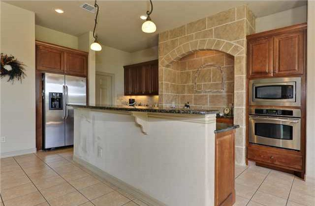 The kitchen is equipped with stainless steel appliances, a two-tier island, wooden cabinetry, and a cooking alcove.