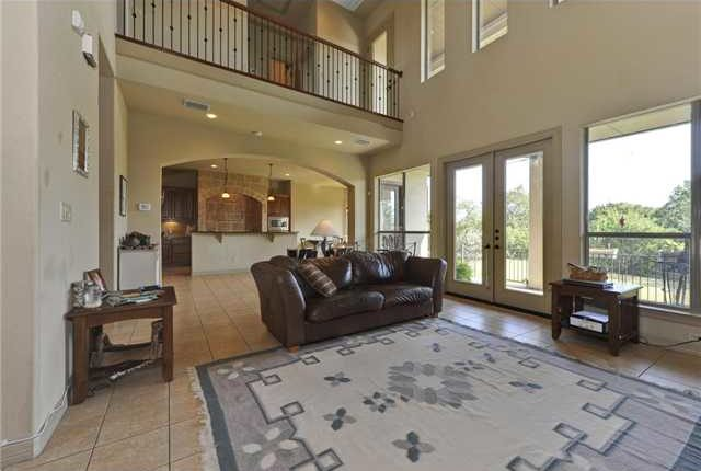 The living room has a leather sofa, wooden tables, a tasseled area rug, and a french door that leads out to the covered patio.