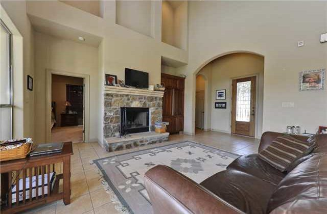 A stone fireplace topped with a TV complete the living room.