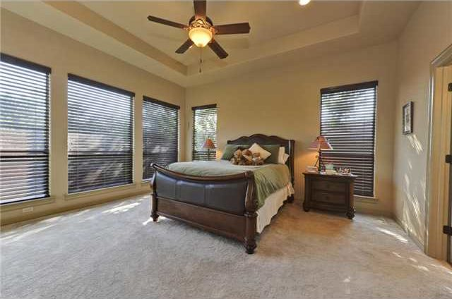 Primary bedroom with wooden furnishings, tray ceiling, carpet flooring, and plenty of windows covered in brown roller blinds.