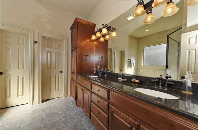 The primary bathroom features a long vanity with dual sink, black granite countertop, and warm glass sconces.