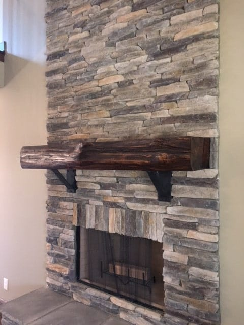 A closer look at the fireplace with stone brick surround and a wooden mantel.