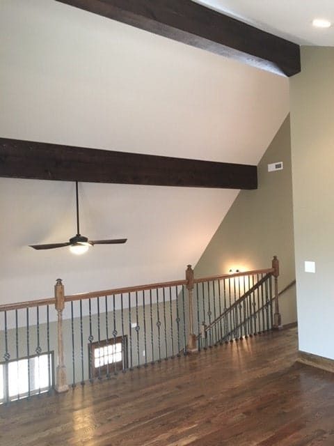 The balcony loft has ornate wrought iron railings and a vaulted ceiling lined with dark wood beams.