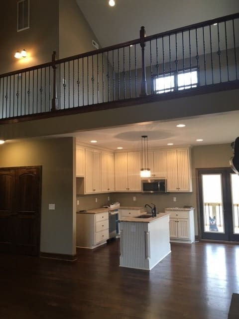 The kitchen is equipped with white cabinets, stainless steel appliances, and a prep island.