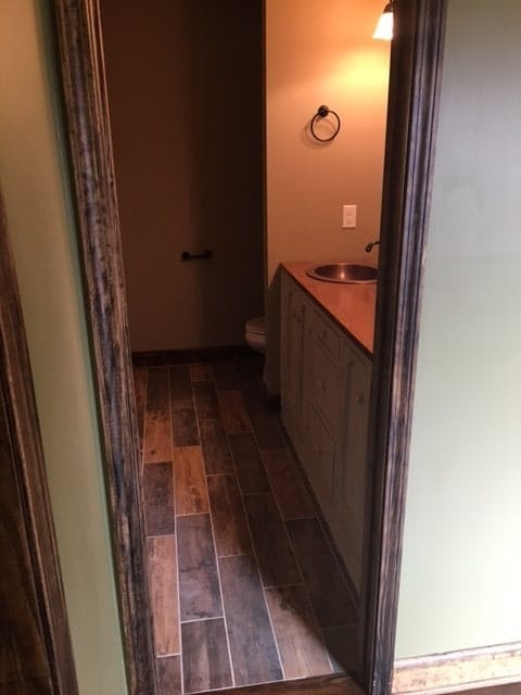 Primary bathroom with wide plank flooring, a toilet area, and dual sink vanity.