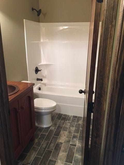 This bathroom has a wooden vanity, a toilet, and a tub and shower combo.