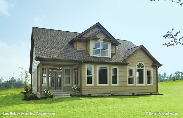 Rear exterior view showing the warm siding, large dormer, and a covered porch.
