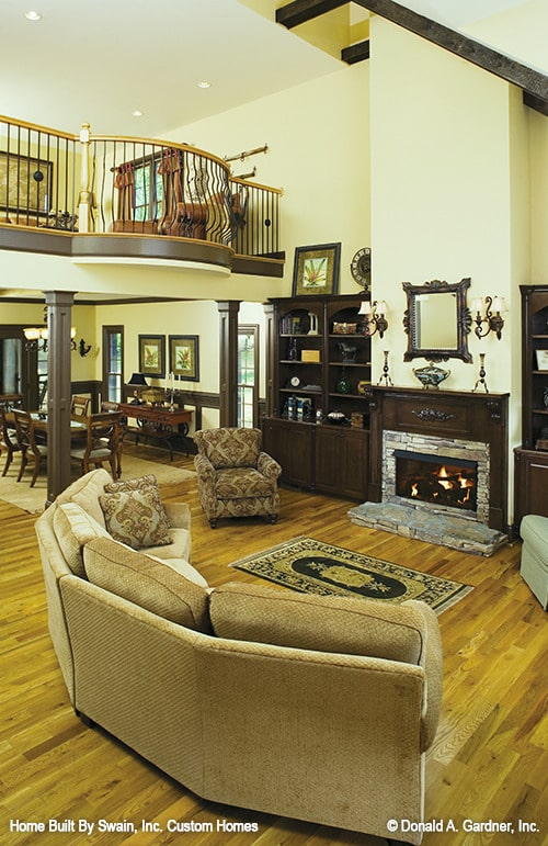 Living room with a curved sectional, patterned armchair, and a stone fireplace flanked by dark wood built-ins.