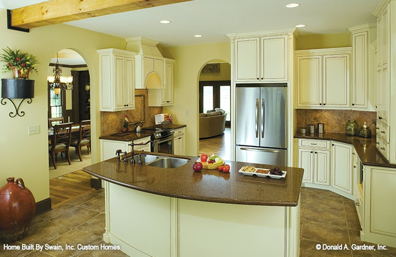 The kitchen is equipped with cream cabinets, stainless steel appliances, granite countertops, and a double bowl sink fitted on the prep island.