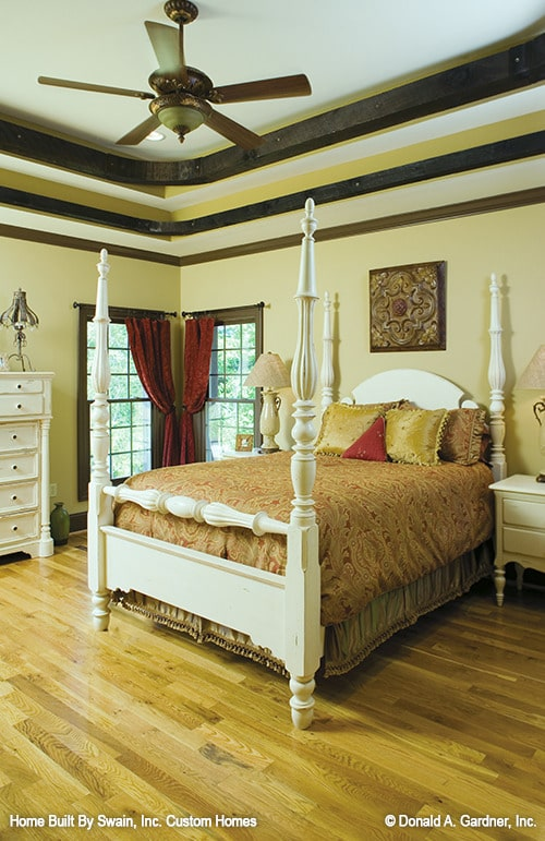 Primary bedroom with white furnishings, corner windows, hardwood flooring, and a striking step ceiling.