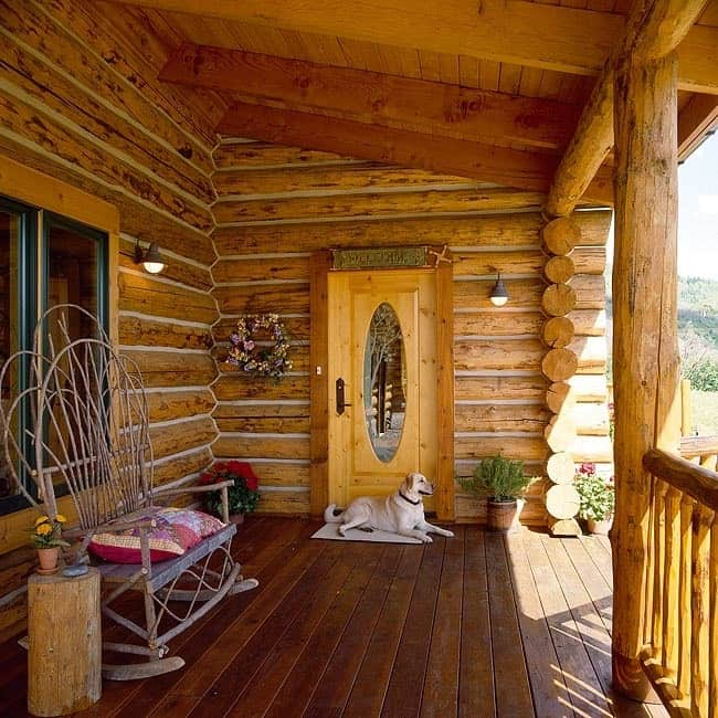 Covered porch with a rustic rocking chair, a log table, and a wooden entry door.
