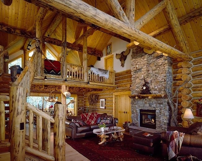 Living room with leather seats, stone fireplace, log walls, and vaulted ceiling framed with wooden beams.