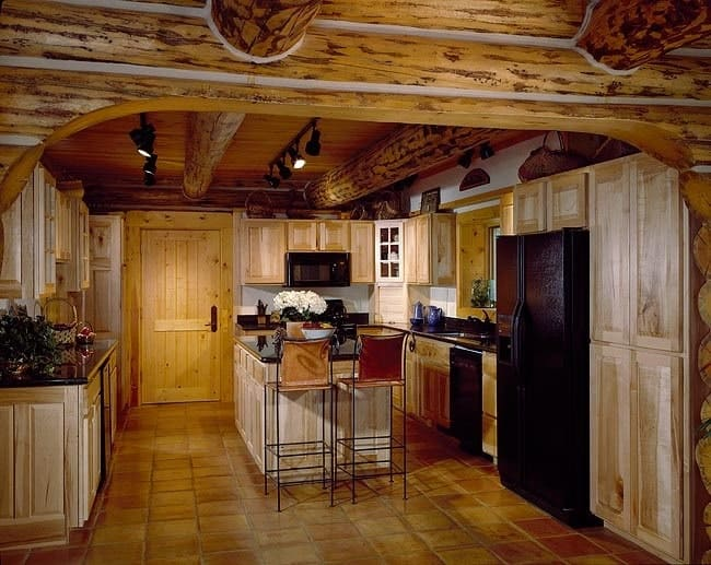 The kitchen has natural wood cabinets, black appliances, and a center island.