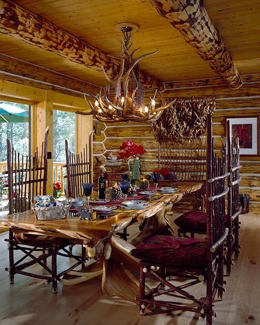 Formal dining room with a stump dining table, unique cushioned chairs, and a driftwood chandelier hanging from the beamed ceiling.