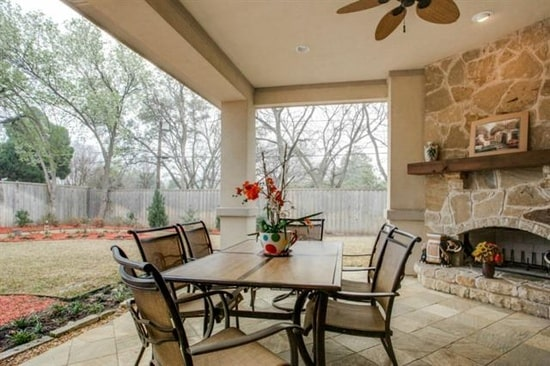 Covered patio with a stone fireplace and wooden dining set over a concrete tiled flooring.