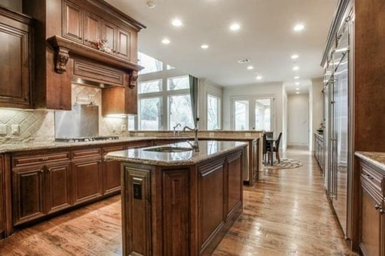 Recessed ceiling lights along with massive glass windows and doors brighten the kitchen.