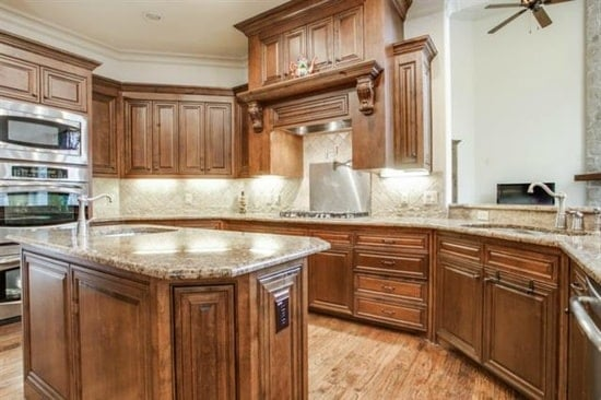 The kitchen is equipped with stainless steel appliances, wooden cabinetry, granite countertops, and a center island fitted with a sink.