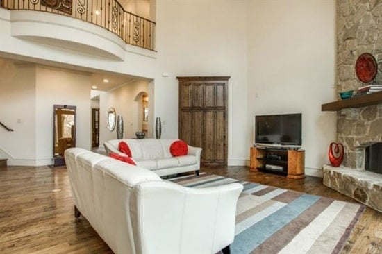 Living room with a two-story ceiling and a natural hardwood flooring topped by a striped area rug.