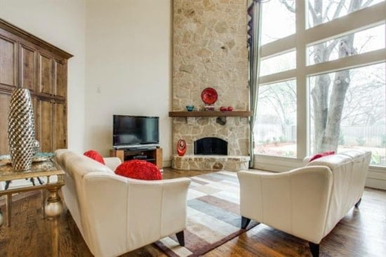 The living room is filled with a stone fireplace, a TV, wooden tables, and beige sofas that are accented with red pillows.