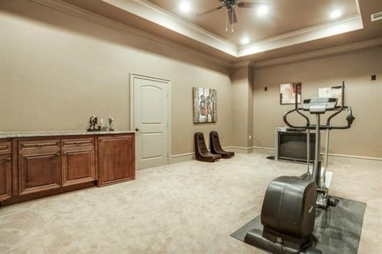 The bonus room is filled with gym equipment, leather seats, a wooden cabinet, and interesting paintings.
