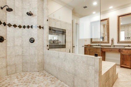 The primary bathroom has a walk-in shower, a dual sink vanity, and a double fireplace fixed above the deep soaking tub.