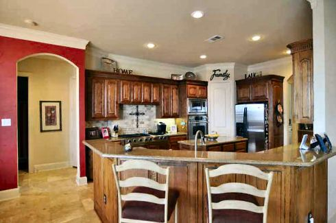 The kitchen is equipped with granite countertops, stainless steel appliances, a center island, and a curved peninsula.