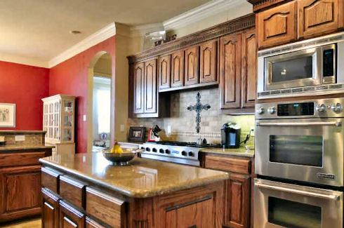 A closer look at the kitchen shows the wall ovens, granite top island, and a cooking range accentuated with tiled backsplash.