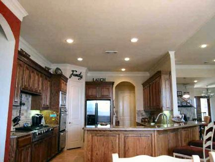 Recessed ceiling lights fitted on the regular ceiling illuminate the kitchen.