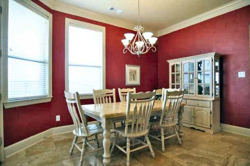 Breakfast nook with red walls, white display cabinet, and a matching dining set well-lit by an ornate chandelier.