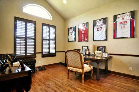 Study with dark wood desks, cushioned chairs, arched transom, louvered windows, and yellow walls adorned by framed jerseys.