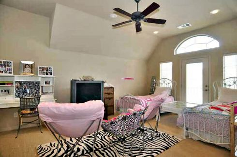 This bedroom offers two beds, a white desk, and metal chairs sitting on a zebra area rug.
