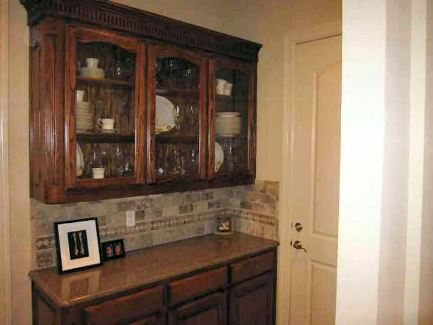 Butler's pantry with wooden and glass front cabinets, granite countertop, and decorative tile backsplash.
