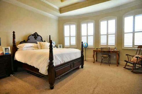 The primary bedroom has a tray ceiling, carpet flooring, four-poster bed, a wooden desk, and a rocking chair.