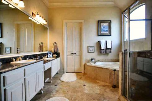 Primary bathroom with a walk-in shower, dual sink vanity, corner tub, and white shaggy rugs that lay on the limestone flooring.