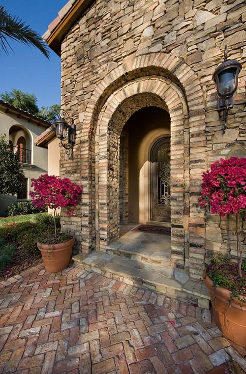 A closer look at the arched entryway complemented with large potted plants and brick paving arranged in a herringbone pattern.