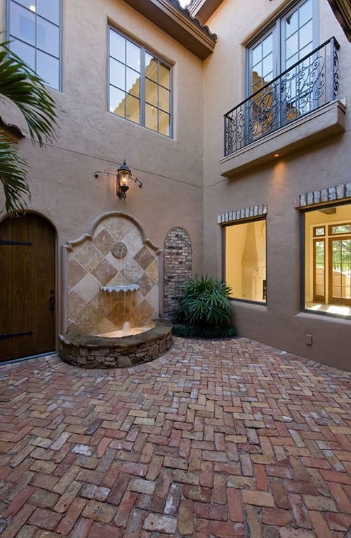 Courtyard with brick flooring and a dazzling fountain with an outdoor sconce on top.