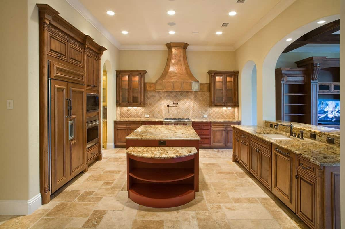 Kitchen with yellow walls, limestone flooring, wooden cabinetry, and granite countertops.