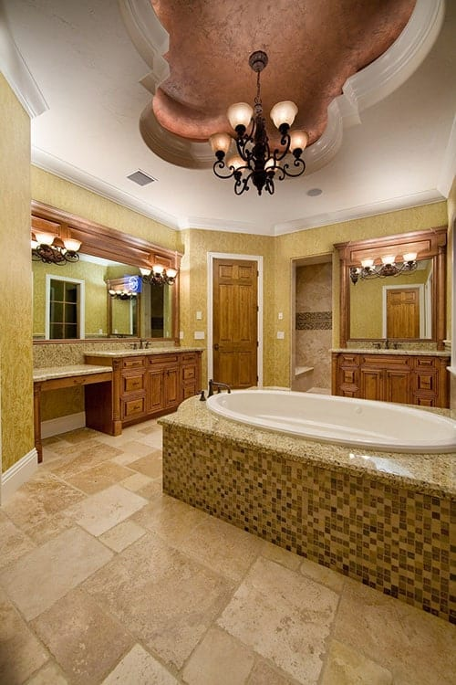 The primary bathroom is equipped with wooden vanities, a deep soaking tub, and an ornate chandelier hanging from the tray ceiling.