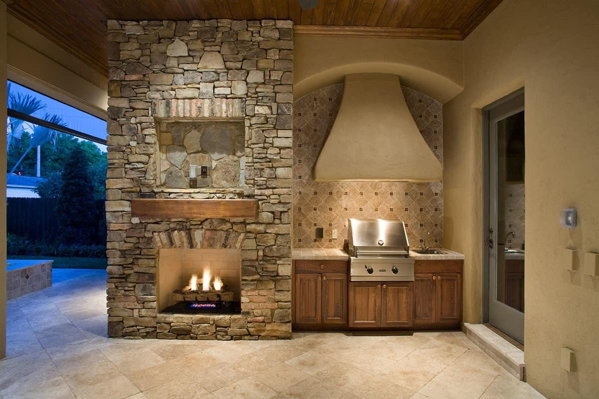 Covered patio with a summer kitchen and a stone fireplace lined with a rustic mantel.