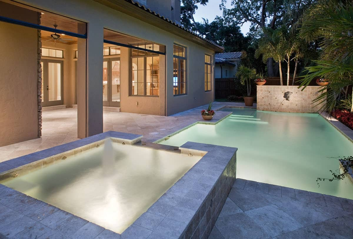 Rear patio with covered lanai and a swimming pool incorporated with a spa.
