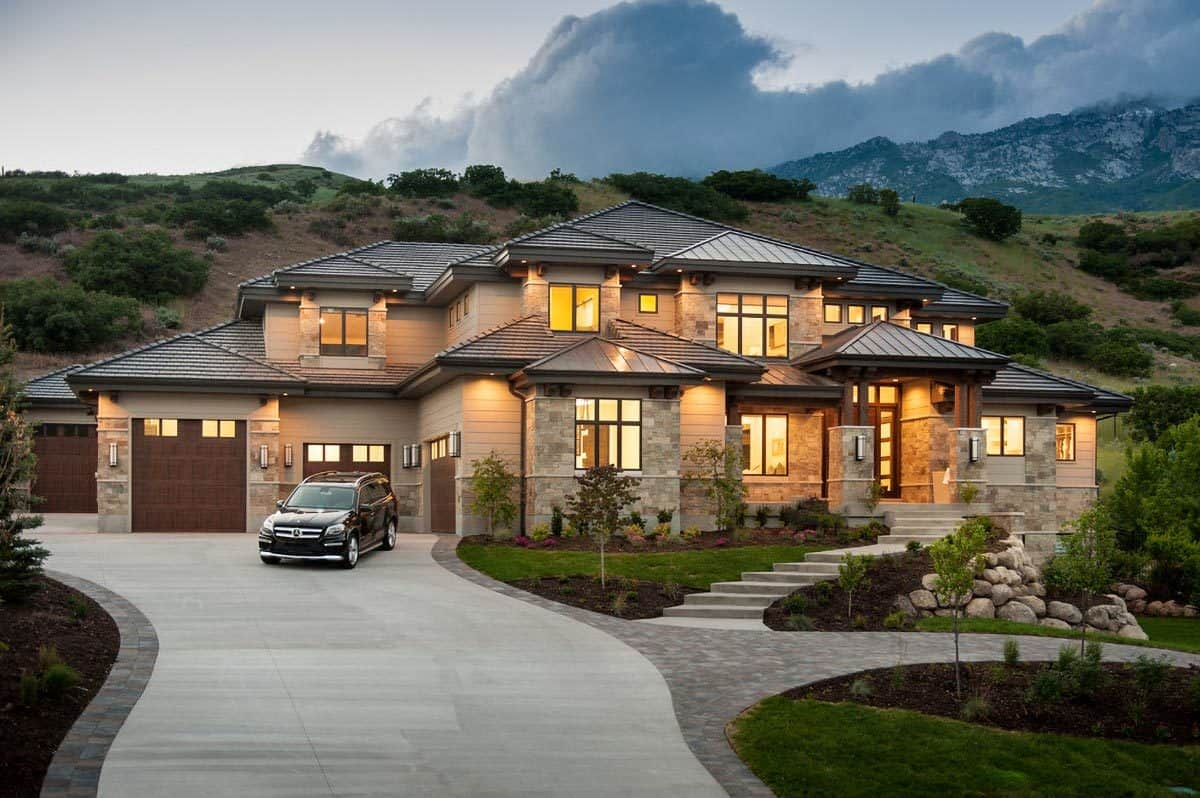 The wide curved driveway leads directly to the L-shaped garages.