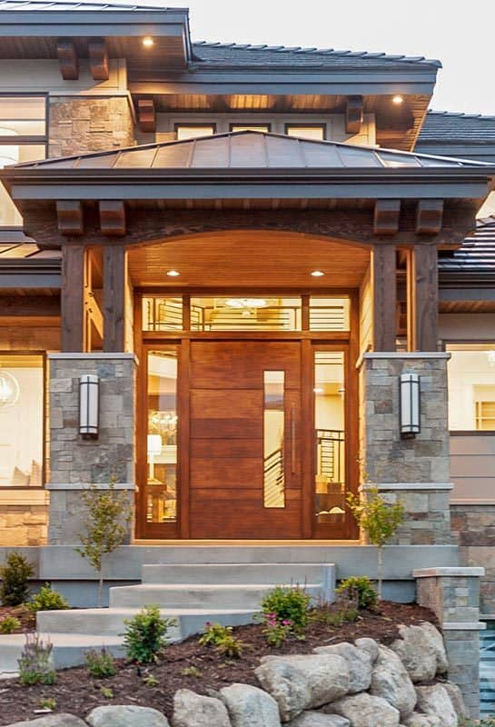 Home entry with the wood-paneled ceiling, outdoor sconces, and a wooden front door surrounded by glass panels.