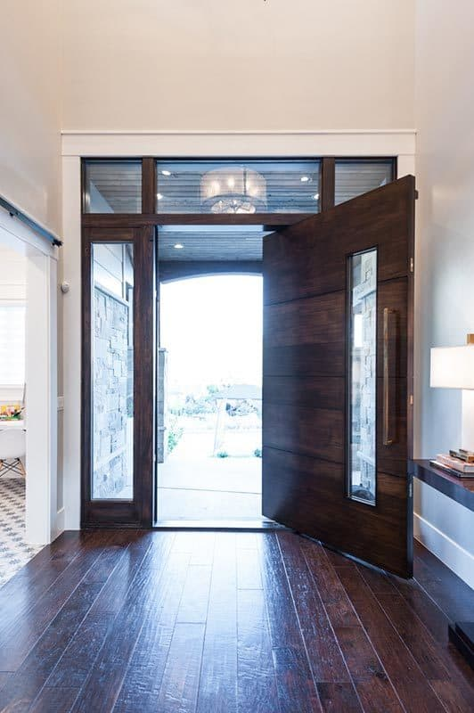 The wooden front door opens to a spacious foyer with wide plank flooring and a wooden console table.
