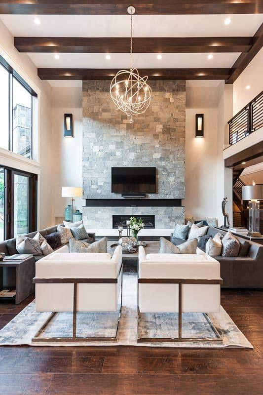 A spherical chandelier that hangs from the beamed ceiling illuminates the living room.