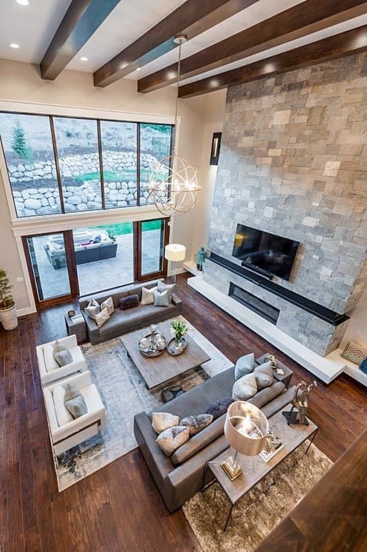 View of the living room from the second-floor balcony showing the natural hardwood flooring topped by area rugs.
