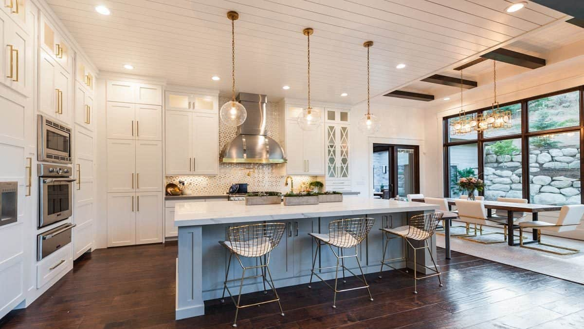Eat-in kitchen with glass globe pendants, stainless steel appliances, breakfast island, and white cabinetry accentuated by brass hardware.