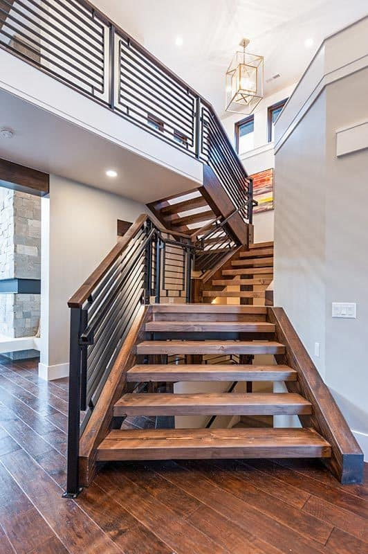 Winding staircase with wrought iron railings, open risers, and wooden treads that blend in with the wide plank flooring.