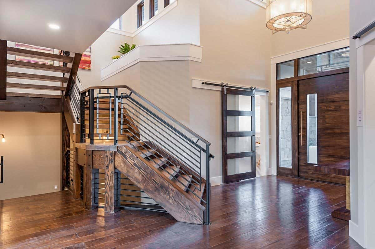 The foyer is filled with a winding staircase, wooden entry door, and a drum chandelier.