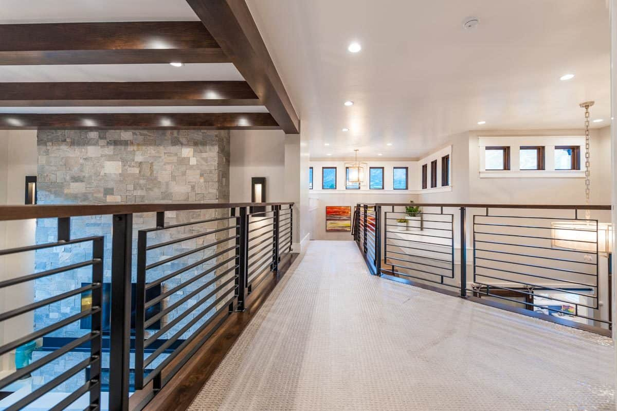 Second-floor balcony with carpet flooring and wrought iron railings overlooking the foyer and living room below.